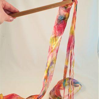 Zijden regenboog slinger van handgeschilderde linten aan een houten stok